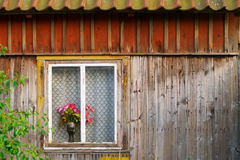 Red roses in a vase standing on a window sill. Royalty Free Stock Photos