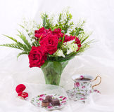 Red roses in vase and vintage teacups Royalty Free Stock Photo