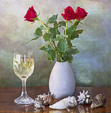 Red roses in vase, white wine glass and shells Stock Photos