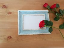 Beautiful Roses With A Vintage Frame. Red roses with a vintage frame laying on a wooden background, Mothers day, Thank you card, Friendship, Love royalty free stock image
