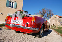 Red roses wedding bouquet. On the red sport's car Royalty Free Stock Photography