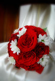 Red roses wedding bouquet. On the white wedding chair cover Royalty Free Stock Photography