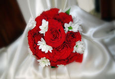 Red roses wedding bouquet. On the white chair cover Stock Image