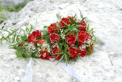 Red roses wedding bouquet. At a white stone Stock Photo