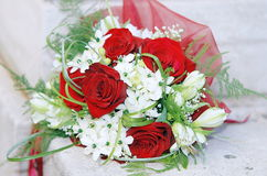 Red roses wedding bouquet. At a white stone Stock Photos