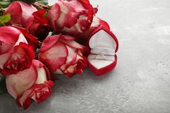 Red roses with wedding ring. Beautiful red roses with wedding ring on grey wooden table Royalty Free Stock Photo
