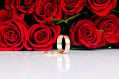 Red  roses and wedding rings. Red  roses and two golden wedding rings Stock Photography