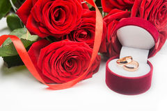 Red roses and wedding rings. On background Stock Photography