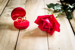 Red roses and wedding rings  on wooden. Background Royalty Free Stock Photo