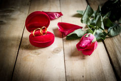 Red roses and wedding rings  on wooden Royalty Free Stock Image