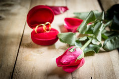 Red roses and wedding rings  on wooden. Background Royalty Free Stock Images