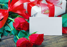 Red roses and white card with a place for a congratulatory text Stock Photo