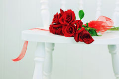 Red Roses on a White Chair Stock Images