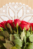 Red Roses on white crochet tablecloth Royalty Free Stock Photography