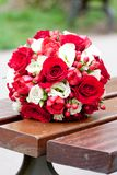 Red roses and white flowers wedding bouquet. On a wooden bench Royalty Free Stock Photo