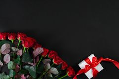 Red roses and white gift box with red ribbon on black background. Top view. Flat lay. Copy space. Still life Stock Photo