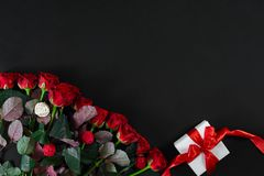Red roses and white gift box with red ribbon on black background. Top view. Flat lay. Copy space. Still life Royalty Free Stock Photo