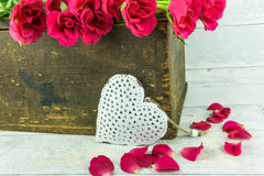 Red roses with a white heart. In a wooden box Stock Image
