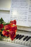Red roses on a white piano with notes. And garlands stock image
