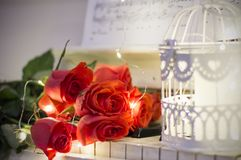 Red roses on a white piano with notes, garlands. And decorative cell stock photography