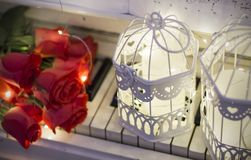 Red roses on a white piano with notes, garlands. And decorative cells stock photography