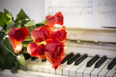 Red roses on a white piano with notes. And garlands stock photography