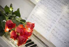 Red roses on a white piano with notes. And garlands stock photos