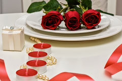 Red Roses on a white plate, candles and giftbox. Romantic composition for Valentine`s Day, Anniversary, Events. Place Royalty Free Stock Images