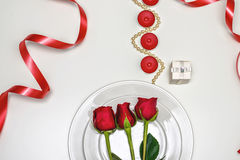 Red Roses on a white plate, candles and giftbox. Romantic composition for Valentine`s Day, Anniversary, Events. Place Stock Photography