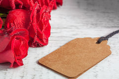 Red roses on white rustic wood with gift tag Royalty Free Stock Photo