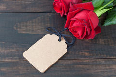 Red roses on white rustic wood with gift tag Royalty Free Stock Photography