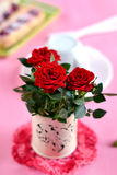 Red roses in a white vase on pink background. And a pastry stock photo