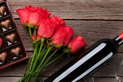 Red roses, wine bottle and chocolate box. Valentines day with red roses, wine bottle and chocolate box on wooden table. Top view with space for your text Royalty Free Stock Photo