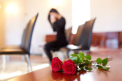 Red roses and woman crying at funeral in church Stock Photos