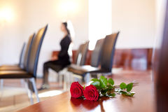 Red roses and woman crying at funeral in church Royalty Free Stock Image
