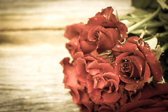 Red roses on wood background. Vintage style. Royalty Free Stock Photos