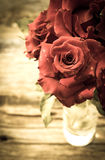 Red roses on wood background. Vintage style. Royalty Free Stock Photo