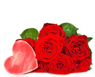 Red roses and wooden heart. Composition on a white background royalty free stock photography