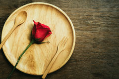 Red roses. On a wooden plate on a wooden table Royalty Free Stock Photos