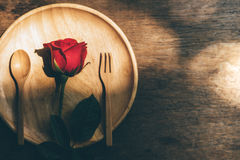Red roses. On a wooden plate on a wooden table Stock Image