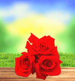 Red roses on wooden table, blurred nature background and green g Royalty Free Stock Images