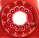 Red Rotary Phone Dial. Bright red retro North American rotary telephone dial with blank center for text Stock Photos