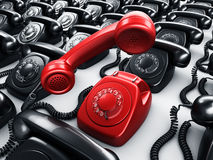 Red rotary phone surrounded by black phones Royalty Free Stock Images