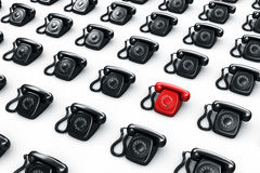 Red rotary phone surrounded by black phones Stock Photos