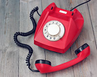 Red rotary telephone off hook on a wooden platform. royalty free stock photos