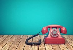 Red rotary telephone on wood table. Against greenish blue wall background. 3D rendering Royalty Free Stock Photo