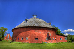 Red Round Barn with Church. A red round barn sits on farm land with church in the background Royalty Free Stock Photography