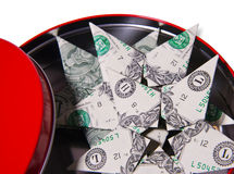 Red round box and dollar stars bills. Dollar bills folded in the shape of origami stars are in the red Royalty Free Stock Photo