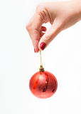 Red round christmas ball in female hand Royalty Free Stock Image