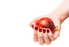 Red round christmas ball in female hand Royalty Free Stock Photography